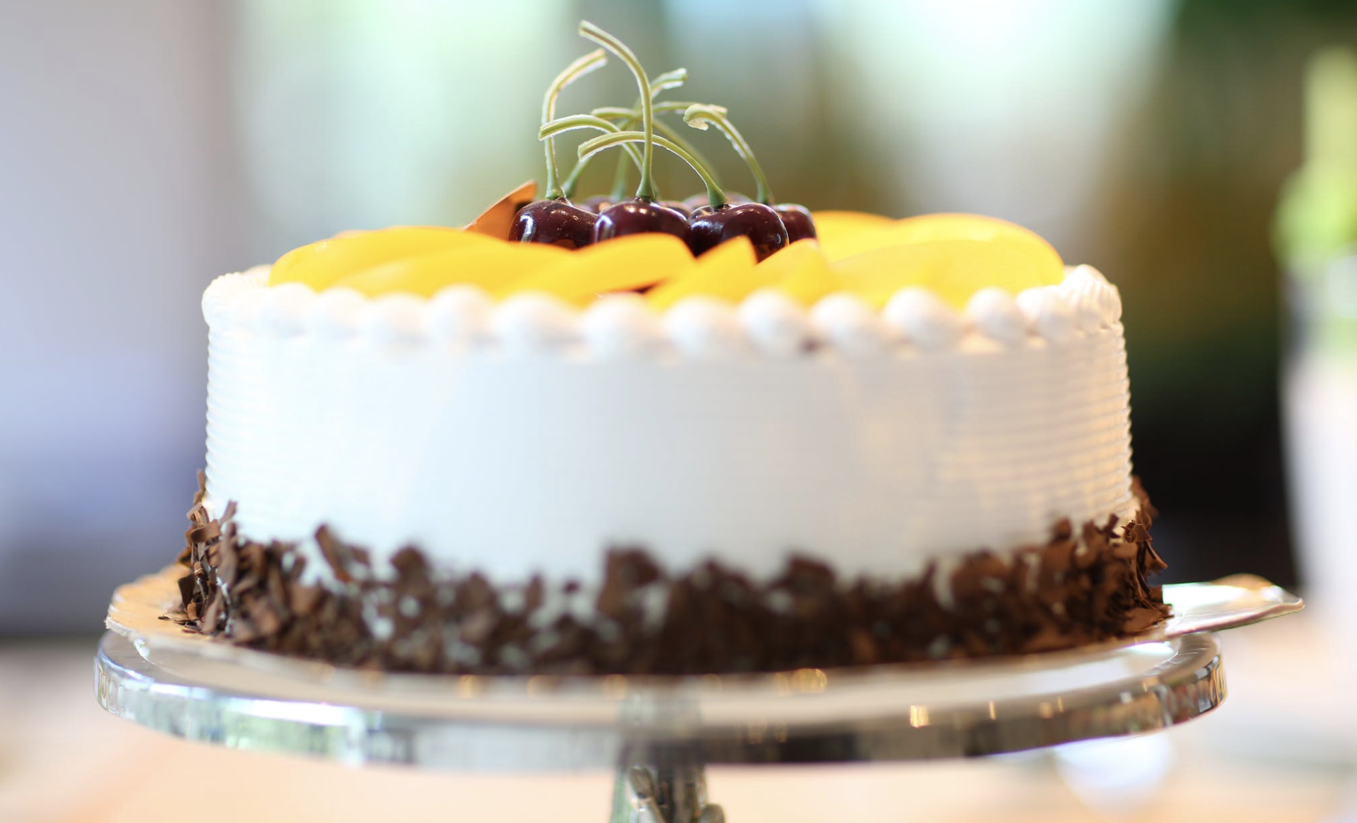 white cake with cheeries on the top
