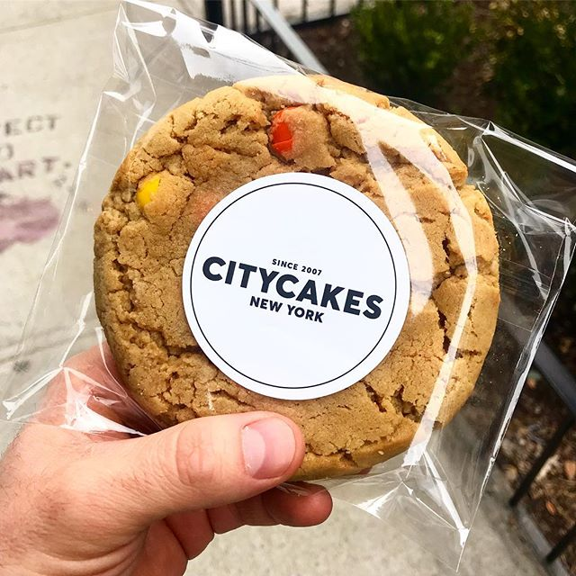 city cakes cookie held by person